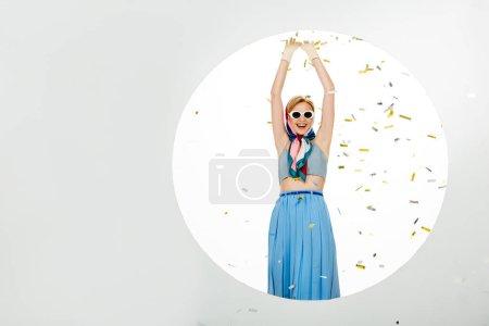 Photo pour Fille positive dans des lunettes de soleil debout près du cercle sous les confettis tombants sur fond blanc - image libre de droit
