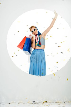Photo pour Femme souriante en foulard et lunettes de soleil tenant des sacs à provisions sous les confettis tombant près du cercle sur fond blanc - image libre de droit