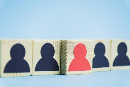 Photo pour Rangée de blocs en bois avec des icônes humaines noires et rouges sur fond bleu, concept de leadership - image libre de droit
