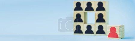 Photo pour Carré de blocs de bois avec des icônes humaines noires et pièce rouge sur fond bleu, mise au point sélective, prise de vue panoramique - image libre de droit