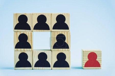 Photo pour Carré de blocs de bois avec des icônes humaines noires et pièce rouge sur fond bleu, concept de leadership - image libre de droit