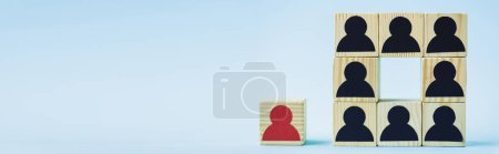 square of wooden blocks with black human icons and red piece on blue background, leadership concept, panoramic shot