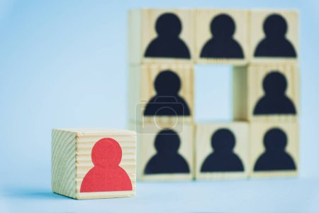 Photo for Square of wooden blocks with black human icons and red piece on blue background, selective focus - Royalty Free Image