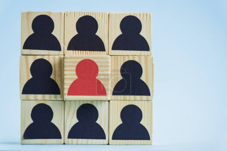 square of wooden blocks with black and red human icons on blue background, leadership concept