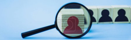 selective focus of magnifying glass near wooden block with red human icon on blue background, leadership concept, panoramic shot