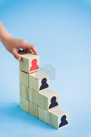 Photo pour Vue recadrée de main touchant pyramide de blocs de bois avec des icônes humaines noires et rouges sur fond bleu, concept de leadership - image libre de droit