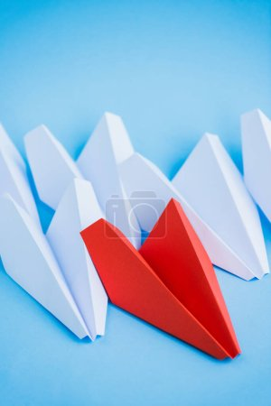 white and red paper planes on blue background, leadership concept
