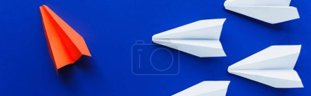 top view of white and red paper planes on blue background, leadership concept, panoramic shot