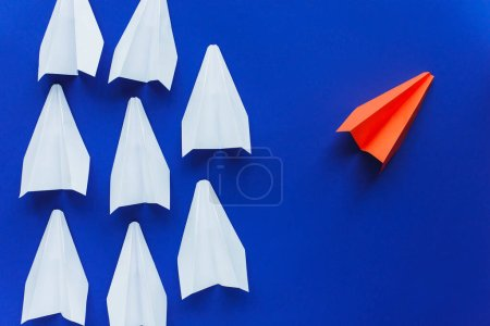 top view of white and red paper planes on blue background, leadership concept