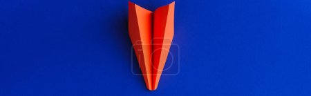 top view of red paper plane on blue background, leadership concept, panoramic shot