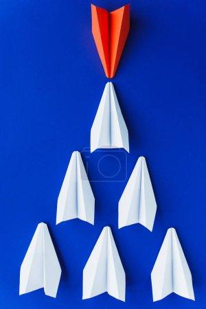 plano con planos de papel blanco y rojo sobre fondo azul, concepto de liderazgo
