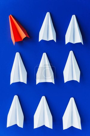 flat lay with white and red paper planes on blue background, leadership concept
