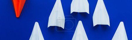 Photo for Top view of white and red paper planes on blue background, leadership concept, panoramic shot - Royalty Free Image