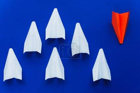 Photo pour Vue du dessus des avions en papier blanc et rouge sur fond bleu, concept de leadership - image libre de droit