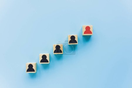 top view of wooden blocks with black and red human icons on blue background, leadership concept