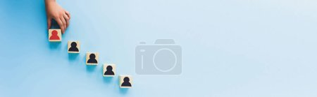 Photo for Partial view of hand and wooden blocks with black and red human icons on blue background, leadership concept, panoramic shot - Royalty Free Image