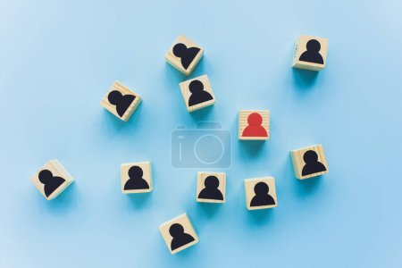 top view of wooden blocks with black and red human icons scattered on blue background, leadership concept