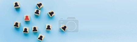 Photo pour Vue de dessus des blocs de bois avec des icônes humaines noires et rouges éparpillées sur fond bleu, concept de leadership, prise de vue panoramique - image libre de droit