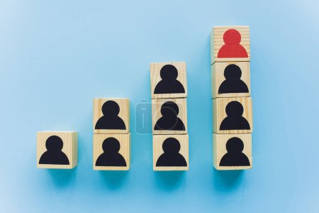 top view of wooden blocks with black and red human icons on blue background, leadership and career ladder concept