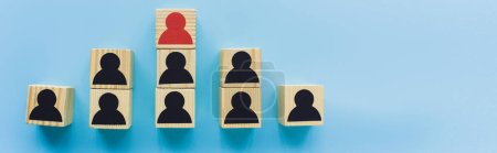 panoramic shot of wooden blocks with black and red human icons on blue background, leadership and career ladder concept