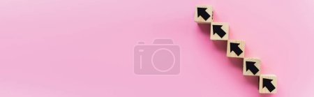 Photo for Panoramic shot of wooden blocks with black arrows on pink background, business concept - Royalty Free Image
