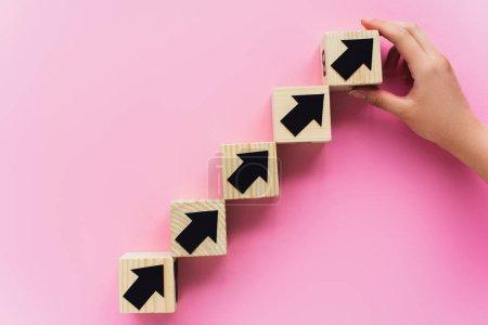 Photo pour Vue partielle de la main près de blocs de bois avec des flèches noires sur fond rose, concept d'entreprise - image libre de droit