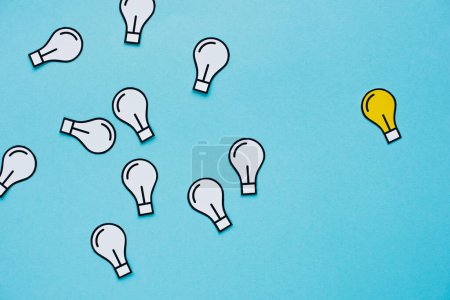 top view of paper light bulbs scattered on blue background, business concept
