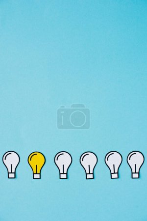 Photo pour Pose plate avec ampoules en papier sur fond bleu, concept d'entreprise - image libre de droit