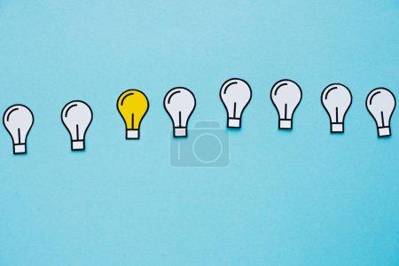 Photo pour Vue du dessus des ampoules en papier sur fond bleu, concept d'entreprise - image libre de droit