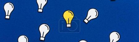 Foto de Plano panorámico de bombillas de papel sobre fondo azul, concepto de negocio - Imagen libre de derechos