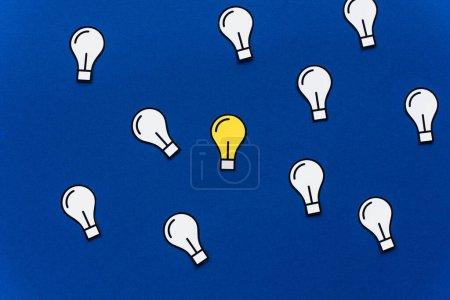 vista superior de las bombillas de papel sobre fondo azul, concepto de negocio