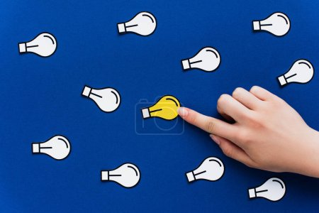 cropped view of hand pointing at paper light bulb on blue background, business concept