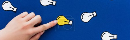 Photo for Cropped view of hand pointing at paper light bulb on blue background, business concept - Royalty Free Image