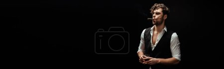 Photo for Panoramic orientation of handsome man in formal wear smoking cigar and holding glass of whiskey isolated on black - Royalty Free Image