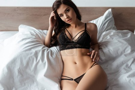 Photo for Sexy girl in bra and panties looking at camera on bed - Royalty Free Image
