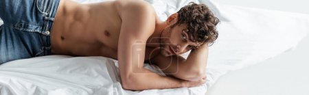 Photo for Panoramic shot of handsome muscular man looking at camera on bed isolated on white - Royalty Free Image