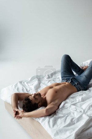 Sexy man in jeans lying on bed on white background