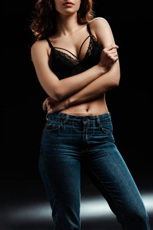 Photo for Cropped view of woman in lace bra and jeans on black background - Royalty Free Image