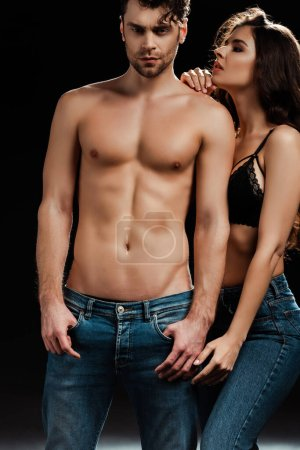 Photo for Sensual girl in bra and jeans standing near handsome shirtless man on black background - Royalty Free Image