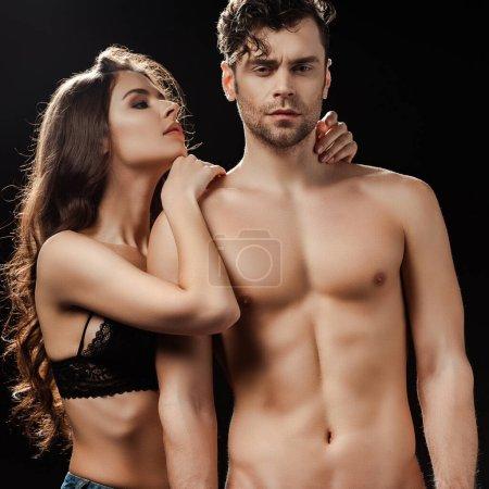 Photo pour Belle femme en soutien-gorge embrassant bel homme torse nu isolé sur noir - image libre de droit