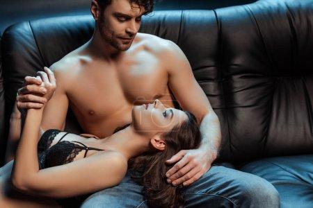 Photo pour Homme torse nu tenant la main de belle fille en soutien-gorge en dentelle sur le canapé sur fond noir - image libre de droit