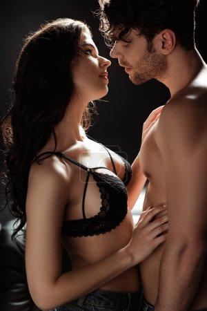 Photo pour Brunette femme en soutien-gorge touchant torse de petit ami sexy sur fond noir - image libre de droit
