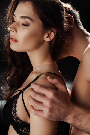 Photo for Shirtless man kissing neck and hugging beautiful woman in bra on black background - Royalty Free Image