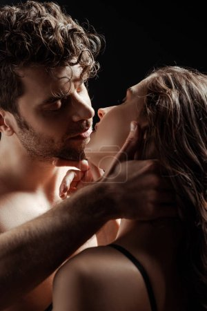 Photo pour Homme torse nu embrasser et toucher petite amie brune isolé sur noir - image libre de droit