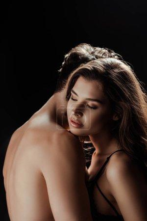 Photo pour Jeune femme en soutien-gorge debout les yeux fermés près de l'homme torse nu isolé sur noir - image libre de droit