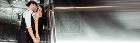 Foto de Orientación panorámica de hombre guapo tocando a mujer sexy en ascensor - Imagen libre de derechos
