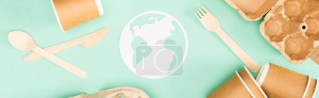 Panoramic shot of disposable tableware and paper earth sign on green background, ecology concept