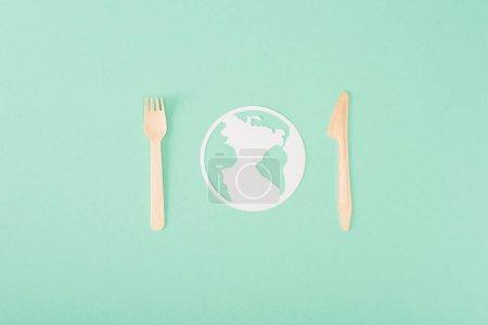 Foto de Vista superior de cubiertos de madera y papel planeta signo sobre fondo verde, concepto de ecología - Imagen libre de derechos