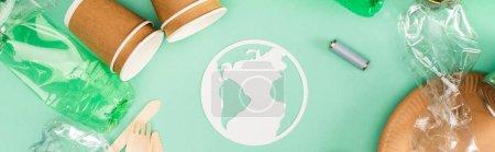 Photo pour Orientation panoramique de signe de terre près de vaisselle jetable, bouteilles en plastique et accumulateurs sur fond vert, concept d'écologie - image libre de droit