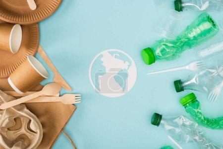 Foto de Vista superior del signo de tierra de papel y vajilla desechable, botellas de plástico y cubiertos sobre fondo azul, concepto de ecología - Imagen libre de derechos